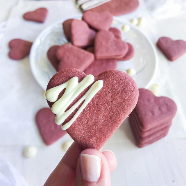 😍 New recipe 👉 Check out these Red Velvet Heart Cookies that are perfect for a treat on ❤️Valentine's day❤️. Baked with love in the shape of love. 😜 You can make any sizes, big or small and decorate it to your liking or just have plain. I made some cookie sandwiches with cream cheese filling. 😊 So good!  I actually had this big idea to fill them with melted marshmallows, but they didn't cooperate yet again.🥴 I'll stay away from marshmallows for a while. 😆  👉 Check out the recipe for Red Velvet Heart Cookies below and tag a friend to give him or her, a hint to bake you some. 👈⁠ ⁠   Recept v 🇸🇮 že na blogu (link v bio). 👍 ⁠  ✨ Red Velvet Heart Cookies ✨  Ingredients: 120 grams of butter 150 grams of icing sugar 1 egg Red food dye (I use one Dr. Oetker Food Colour Gel Red, 10 grams) Vanilla extract 1 table spoon of cocoa powder (about 10 grams) 300 grams of flour 7 grams of baking powder (half a bag) Pinch of salt Additional flour for rolling out the cookie dough Filling: 180 grams of cream cheese 30 grams of icing sugar Decorating: White chocolate Instructions: Make sure your butter is at room temperature and you can mix icing sugar in. Add vanilla, pinch of salt, egg, red food dye and mix again until smooth. In a separate container add flour, cocoa powder, baking powder and stir. Then add the flour mixture to the butter mixture and stir for as long as you can, then knead it into ball shaped dough with your hands. (store in a refrigerator for about 20 minutes if you want) Roll out the dough while sprinkling some flour on both sides, so it doesn't stick. Cut heart shaped cookies, place them on baking paper on a baking tray and bake in a preheated oven on 180 degrees Celsius.  I baked small hearts for 8 minutes and the big ones for 10.  When cookies are baked, leave them to cool down. They are tasty on its own but you can also make sandwich cookies with cream cheese filling, decorate them with white chocolate or other if you want. For making cookie sandwiches just stir cream cheese with icing sugar and spread or pipe the filling on one cookie, then closing the sandwich with another cookie.  Time – 2 hours Quantity – 88 individual heart cookies