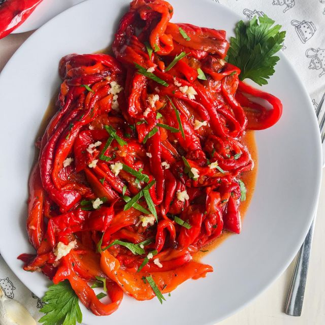 New recipe! 😋😋This beautiful 😍red salad with sweet and smoky flavor is so delicious you will be tempted to eat up the whole bowl.🙂 It is easy to make but takes a little time and patience as you need to remove the seeds and skin of baked red peppers. But so worth the hassle!   👉 Check out the recipe below and tag a friend who would love this recipe.👈   Recept v 🇸🇮 bo kmalu na blogu (link v bio).👍  Let me know if you will make this by tagging me @t_as_tasty, so I can see it. 👍  ✨ Roasted Red Pepper Salad ✨  1500 grams of red long peppers 2 cloves garlic 2 tablespoons olive oil 2 sprigs of parsley Sol Black pepper Instructions: Arrange the peppers on a baking sheet with baking paper. Preheat the oven to 220 degrees Celsius. Then bake the peppers in a higher position in the oven, closer to the heater, for about 25 to 30 minutes. (depending on the size of the peppers) Roast them until they turn a little black. Only then will the skin be removed nicely. Then remove from the oven and let them cool a bit. While still lukewarm, remove the skin by pulling it down with your fingers and then remove the middle and seeds. Excess water dropped by the peppers is also discarded. Cut the roasted peppers into strips and place them in a bowl. Season it with salt and pepper to taste, add oil. Peel the garlic and grate it, chop the parsley and add it all together and mix well. Refrigerate for a couple of hours or overnight, then serve. Time - 1 hour + cooling Quantity - 3 servings